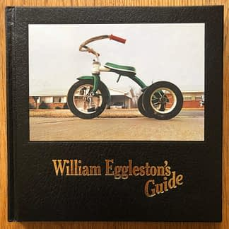 The photography book cover of William Eggleston's Guide by William Eggleston. In hardcover black with a tricycle.